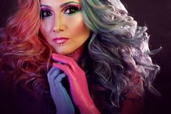 Beautiful woman with bright hair. Body painting and bright hair coloring. Beautiful woman with bright hair. Bright hair color, hairstyle with the curls Royalty Free Stock Images