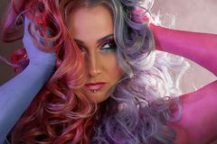 Beautiful woman with bright hair. Body painting and bright hair coloring. Beautiful woman with bright hair. Bright hair color, hairstyle with the curls Stock Photo