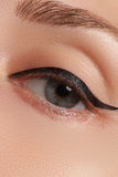 Beautiful woman with bright make up eye with sexy black liner makeup. Fashion arrow shape. Chic evening make-up. Makeup beauty wit Royalty Free Stock Image