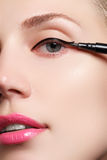 Beautiful woman with bright make up eye with sexy black liner makeup. Fashion arrow shape. Chic evening make-up. Makeup beauty wit Royalty Free Stock Images