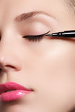Beautiful woman with bright make up eye with sexy black liner makeup. Fashion arrow shape. Chic evening make-up. Makeup beauty wit Stock Photography