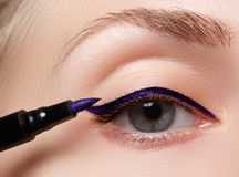 Beautiful woman with bright make up eye with sexy blue liner makeup. Fashion arrow shape. Chic evening make-up. Makeup beauty wit. H brush eye liner on pretty Royalty Free Stock Images
