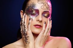 Beautiful woman with bright makeup with glitter. Beautiful young woman with bright colorful makeup with sparkling glitter and hair pattern on face. hands with Royalty Free Stock Photo