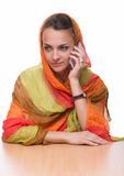 The beautiful woman in a bright multi-colored shawl holds the mobile phone in hand. The beautiful young woman in a bright multi-colored shawl holds the mobile royalty free stock photos