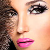 Beautiful woman with bright professional make-up. With feathers near the face stock photography