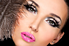 Beautiful woman with bright professional make-up. With feathers near the face royalty free stock photos