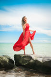 Beautiful woman in a bright red dress by the sea. Stock Images