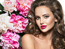 Beautiful woman with bright red lips and flower near the face Royalty Free Stock Images