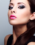 Beautiful woman with bright smokey makeup eyes and pink lipstick. Perfect closeup make-up and foundation Royalty Free Stock Photos