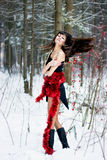 Beautiful woman with bright tinsel in winter forest Royalty Free Stock Images