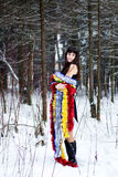 Beautiful woman with bright tinsel in winter forest Royalty Free Stock Photos