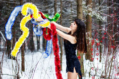 Beautiful woman with bright tinsel in winter forest Stock Photos