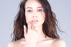 Beautiful woman with brown curly hair and clean skin touching her face Stock Images