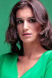 Beautiful woman with brown curly long hair in green dress royalty free stock photos
