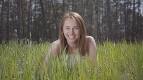 Beautiful woman with brown hair in the green grass around spectacular forest laughing. Beautiful woman with brown long hair in the green grass around spectacular stock video footage