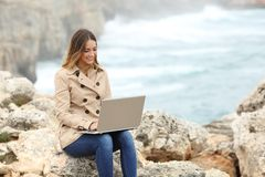 Beautiful woman browsing her laptop in winter on the coast Royalty Free Stock Images