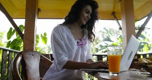 Beautiful woman browsing internet using laptop on terrace in morning, young girl happy smiling typing message on stock footage