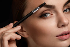 Beautiful Woman Brushing Eyebrows With Brush. Beauty Royalty Free Stock Images