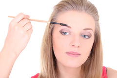 Beautiful woman brushing eyebrows with makeup brush over white Royalty Free Stock Photography