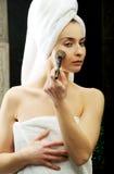 Beautiful woman brushing her cheek. Royalty Free Stock Photos
