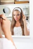 Beautiful woman brushing her eyebrow Royalty Free Stock Photography