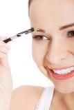 Beautiful woman brushing her eyebrow. Stock Photo