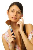 Beautiful woman is brushing her face. Royalty Free Stock Photography