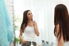 Beautiful woman brushing teeth near mirror in bathroom. At home royalty free stock photos