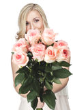Beautiful woman with a bunch of pink roses. Beautiful happy blond woman with a large bunch of beautiful fresh pink roses in her outstretched hands smiling at the Stock Photo