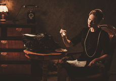 Beautiful woman burning letter in retro interior royalty free stock image
