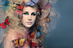 Beautiful woman with butterfly in big curly hair.