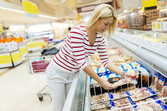 Beautiful woman buying food in supermarket Stock Images