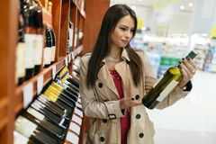 Beautiful woman buying wines. In supermarket stock image