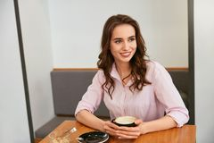 Beautiful Woman In Cafe Drinking Coffee stock images