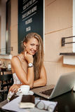 Beautiful woman in cafe with laptop smiling Stock Photo