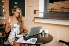 Beautiful woman in cafe with laptop smiling Royalty Free Stock Images