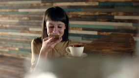 Beautiful woman at cafe making voice message with cell phone and drinking coffe or tea. stock video