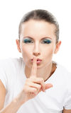 Beautiful woman calls for silence. Young beautiful woman calls for silence, lifting forefinger to lips, on white background Stock Photo