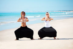 Beautiful woman in cambodian pants. Two young beautiful woman in cambodian pants doing yoga exercises Royalty Free Stock Photos