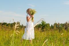 Beautiful woman in a camomile field Stock Photo