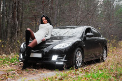 Beautiful woman on car. Beautiful dark-haired woman on black car in autumn forest Stock Photo