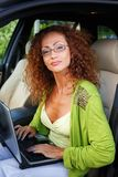 Beautiful woman in car with laptop Stock Photography
