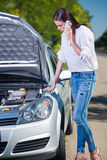 Beautiful woman with car trouble talking over phone Royalty Free Stock Image
