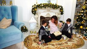 Beautiful woman and caring mother with two male children exchanging New Year`s gifts and sitting on floor in living room. Happy mother and successful woman with stock video