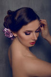 Beautiful woman with carnation flower in her hair Stock Photography