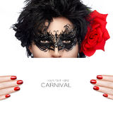 Beautiful woman in carnival mask, copy space. High fashion concept close-up portrait of beautiful brunette wearing black mask, beauty makeup, with nail art and royalty free stock photography