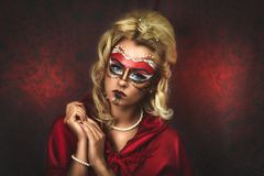 Beautiful Woman Carnival Mask. Portrait of beautiful young girl with new creative make up carnival mask, hands near face, blonde hairstyle. Louis court intrigues Stock Photography