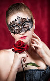 Beautiful woman in carnival mask with red rose Royalty Free Stock Photos