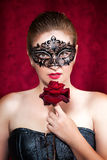 Beautiful woman in carnival mask with red rose. Portrait of beautiful woman in carnival mask with red rose stock photo
