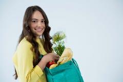 Beautiful woman carrying grocery bag Royalty Free Stock Photos